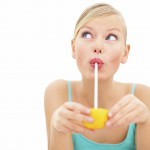 Young charming girl sipping orange juice with a straw over white